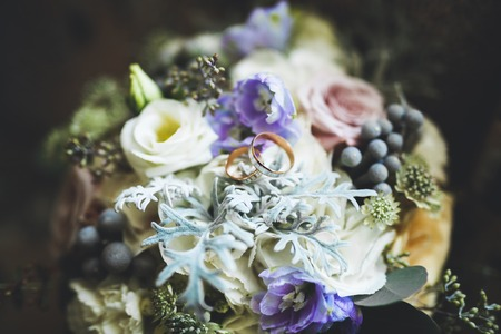 Beautiful toned picture with wedding rings against the background of a bouquet of flowers.