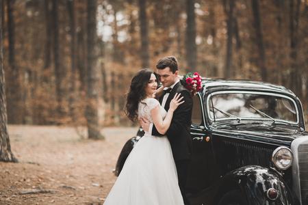 Stylish wedding couple, bride, groom kissing and hugging near retro car in autumn Stock Photo