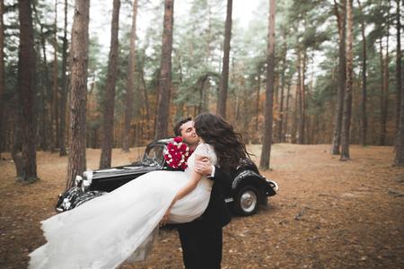 Beautiful wedding couple posing near splendid retro car