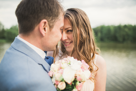 Bride and groom holding beautiful wedding bouquet. Lake, forest