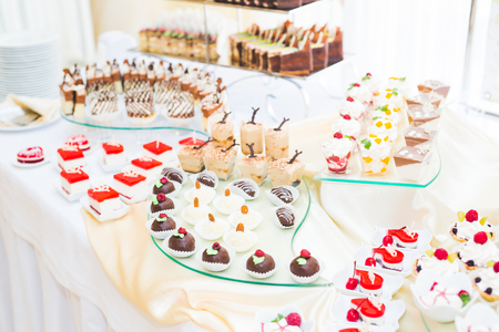 Delicious sweets on wedding candy buffet with desserts, cupcakes. Stock Photo - 107150049
