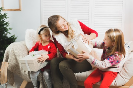 Mother and little kids opening Christmas presents. Living room. Cozy winter evening at home