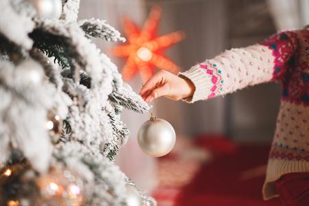 Happy girl decorating a beautiful Christmas tree