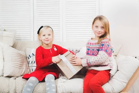 Magic gift box and a child baby girls, Christmas miracle, little beautiful happy smiling girl opens a box with gifts