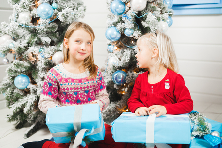 Happy little kids opening presents on Christmas eve