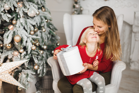 Merry Christmas and Happy Holidays. Cheerful mom and her cute daughter girl exchanging gifts