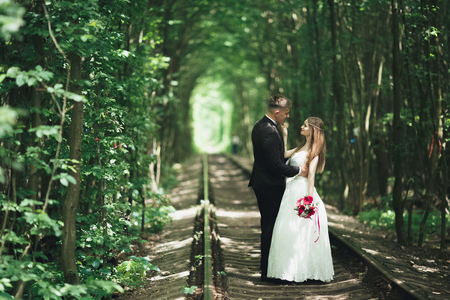 Young wedding couple, bride and groom posing on a railway track