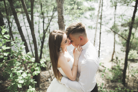 Wedding couple man, bride kissing and hugging on a background of the river, mountains. Beauty portrait