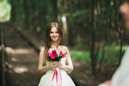Beautiful bride posing on her wedding day in park
