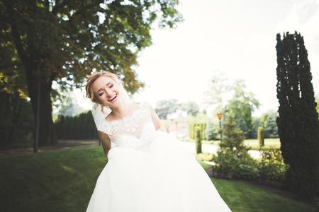 Beautiful bride posing in wedding dress outdoors Stock Photo