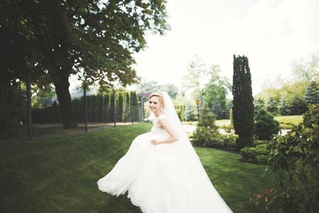 Beautiful bride in elegant white dress holding bouquet posing in park Stock Photo