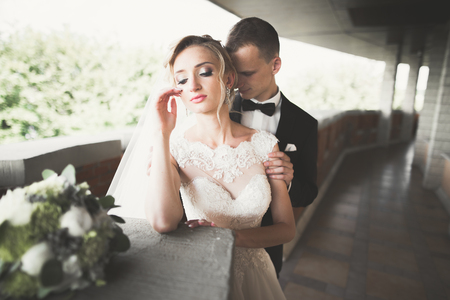 Lovely happy wedding couple, bride with long white dress posing in beautiful city