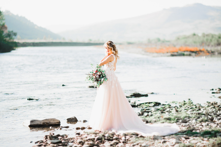 Portrait of stunning bride with long hair standing by the river Stock Photo