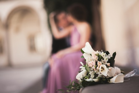 Wedding flowers bouquet with newlywed couple on background Stock Photo