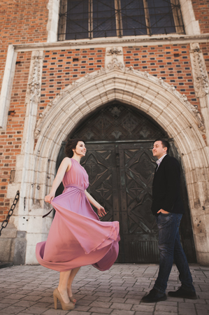 Gorgeous wedding couple, groom and bride with pink dress walking in the old city of Krakow