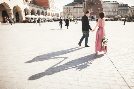 wedding. beautiful couple, bride with pink dress walking in the old city Krakow, their shadows Stock Photo