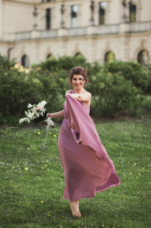 The beautiful woman, bride in pink dress with great bouquet