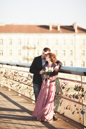 Stylish loving wedding couple, groom, bride with pink dress kissing and hugging on a bridge at sunset Stock Photo