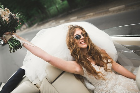 Happy bride in the retro car posing on her weeding day Stock Photo