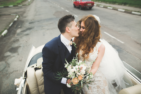 Stylish wedding couple, bride, groom kissing and hugging on retro car