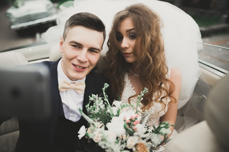 Happy bride and groom making selfie at their wedding in retro car Stock Photo