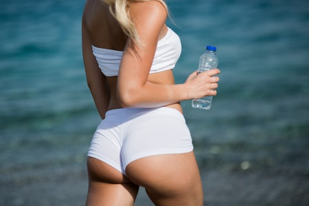 Beautiful young woman with long blond hair in white shorts is standing a back on the coastline of the sea. Stock Photo