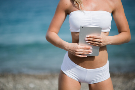Young beautiful woman in sport suit is using her tablet on the beach.