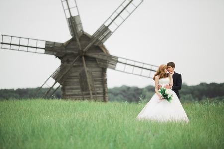Emotional beautiful bride hugging newlywed groom at a field closeup