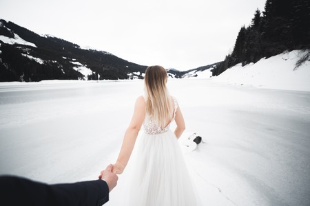 Beautiful young woman bride holds the hand of a man on the background of the mountains. Follow me