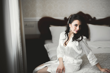 Gorgeous bride in robe posing and preparing for the wedding ceremony face in a room Stockfoto