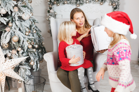 Mother with her child daughters celebrating near Christmas tree
