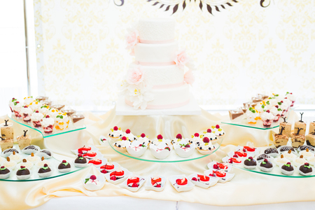 Delicious sweets on wedding candy buffet with desserts, cupcakes Stock Photo - 116918481