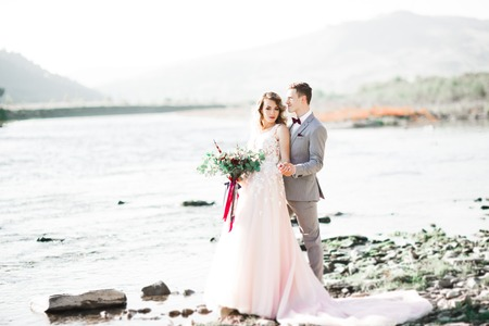 Romantic, fairytale, happy newlywed couple hugging and kissing with trees and river in background