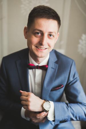 Beautiful man, groom posing and preparing for wedding