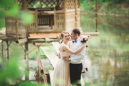 wedding pair hugging and kissing at the bridge