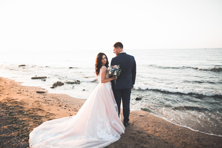 Huwelijkspaar, bruidegom, bruid met boeket het stellen dichtbij overzees en blauwe hemel