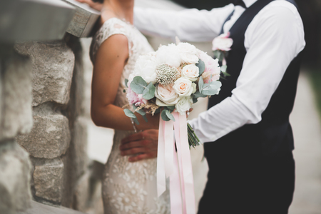 Perfect wedding couple holding luxury bouquet of flowers.