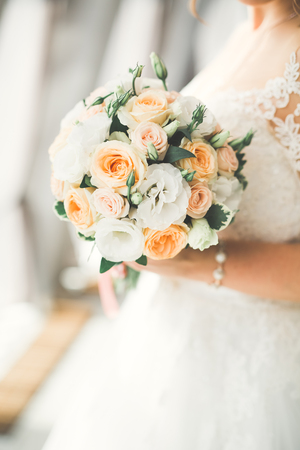Bride holding big and beautiful wedding bouquet with flowers