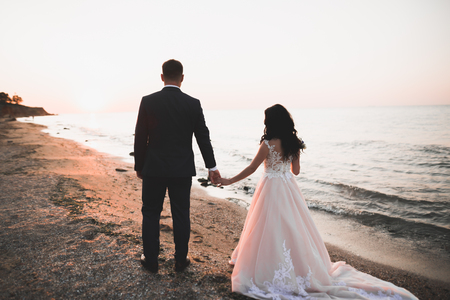 Happy and romantic scene of just married young wedding couple posing on beautiful beach.