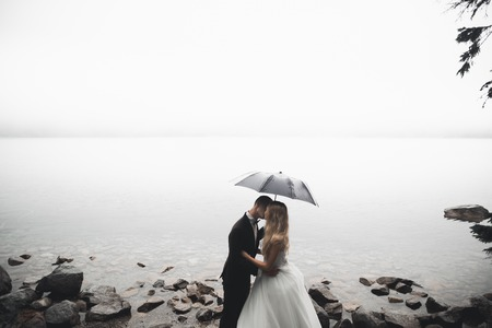 Happy and romantic scene of just married young wedding couple posing on beautiful beach