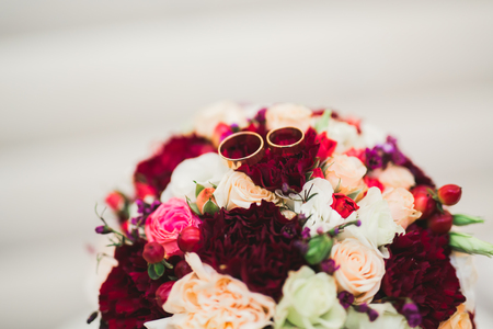 Beautiful toned picture with wedding rings against the background of a bouquet of flowers Imagens