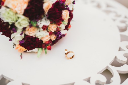 Beautiful toned picture with wedding rings against the background of a bouquet of flowers 写真素材