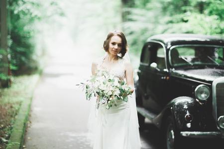 Happy bride in the retro car posing on her weeding day 版權商用圖片