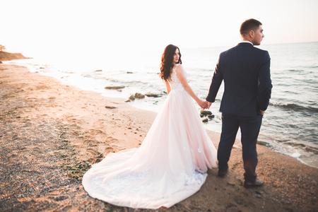 Couple de mariage heureux élégant élégant, mariée, marié magnifique sur fond de mer et de ciel