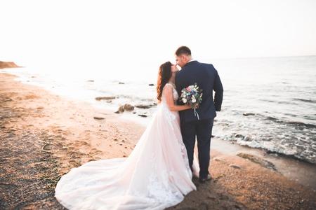 Wedding couple, groom, bride with bouquet posing near sea and blue sky Banco de Imagens