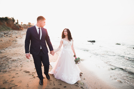 Wedding couple, groom, bride with bouquet posing near sea and blue sky 版權商用圖片