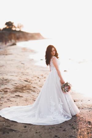 Romantic beautiful bride in white dress posing on the background sea 版權商用圖片