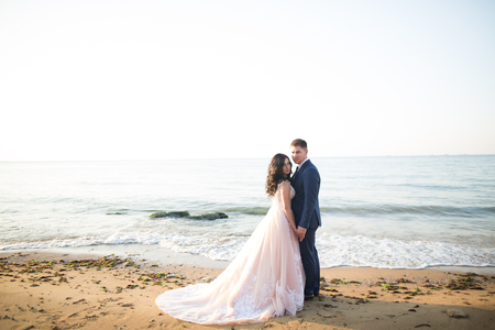 Elegant stylish happy wedding couple, bride, gorgeous groom on the background of sea and sky Imagens