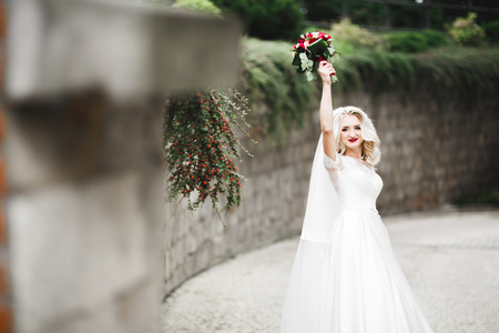 Beautiful bride in elegant white dress holding bouquet posing in park Imagens