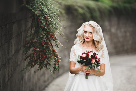 Beautiful luxury young bride in wedding dress posing in park